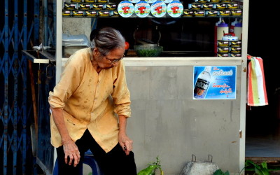Laos. Vientiane. Lady and the fire on the street